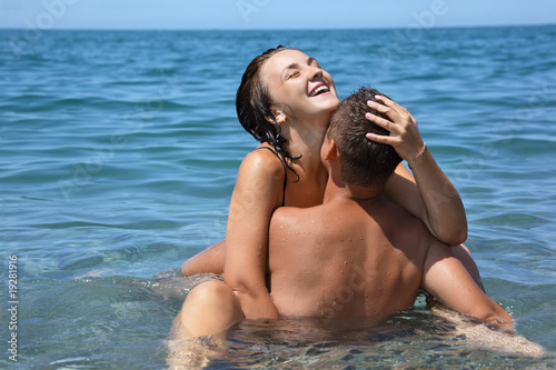 young hot woman sitting astride man in sea near coast, closed ey Poster