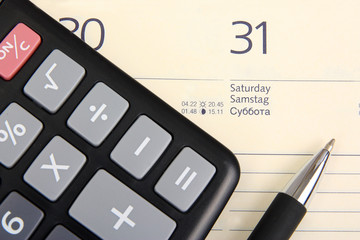 Calendar showing 31, electronic calculator and pencil