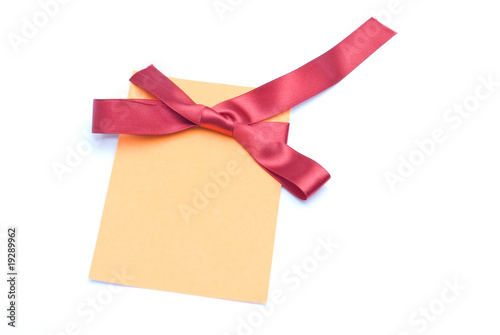 Blank gift tag tied with a bow of red satin ribbon.