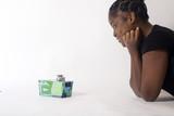 jeune femme noire allongée regarde un cadeau noël