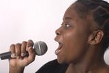 jeune femme noire chante dans un micro emotion
