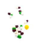 Multicolored defocused medicine pills on the white poster