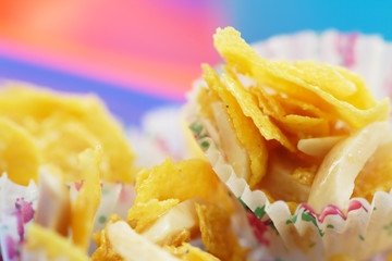 Cornflakes cookies with almond strips on colourful background