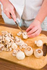 The woman cuts mushrooms