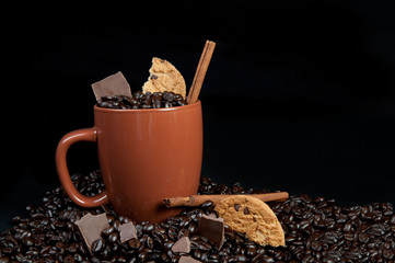 Coffee cup fill of beans, chocolate and cookie