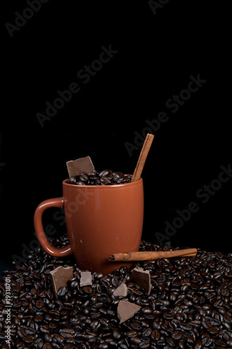 Coffee cup fill of beans, chocolate and cinnamon sticks