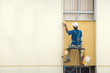 Hanging Painter painting wall with brush