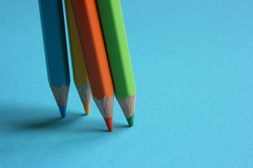 Four color pencils pointed on a blue paper