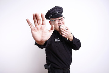Police officer gesturing to stop while eating donut