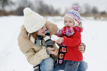 Little winter baby girl and her mother