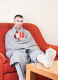 man with a broken leg on a sofa at home  holding cp of coffee
