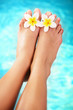 Beautiful pedicured female feet and tropical flowers