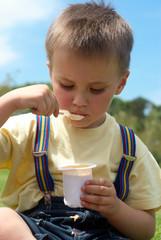 The little boy is appetizing eats yoghurt sitting on a grass in