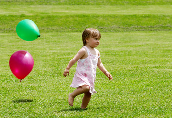 The little girl running on a grass with balloons