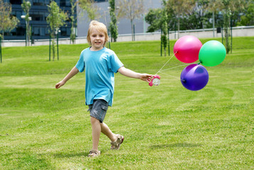 The little boy running on a grass with balloons
