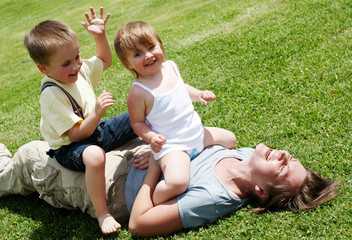 Happy mother playing with children on a lawn