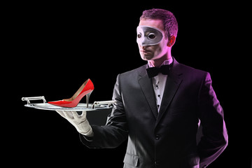 Butler with a mask holding a tray with high heel on it