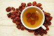 A cup of chinese red date tea with pitted dates around the cup