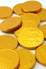 Chocolate gold coins, scattered on white background