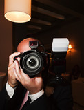 Paparazzi photographer holding an SLR camera with flash poster