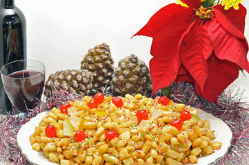 Festive table with Italian Struffoli, wine and pinecones