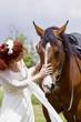 Frau im Hochzeitskleid mit Pferd
