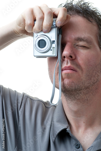 Man shooting with small digital camera on white