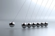 Metal pendulum balls balancing from strings in Newton's cradle