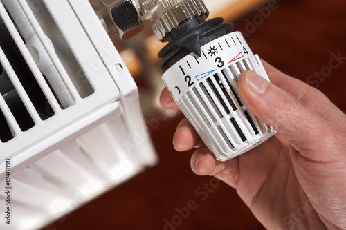 Leinwandbild Motiv adjusting the radiator thermostat