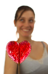 Happy young woman behind heart shaped lollipop