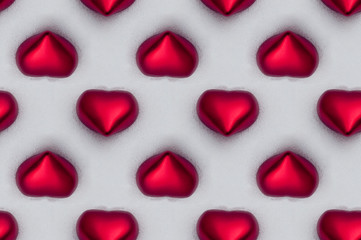 seamless tile of red shiny hearts in the snow