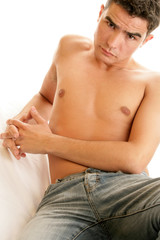 Young barechested man lying on bed