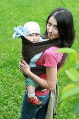 Mother carrying her baby in sling