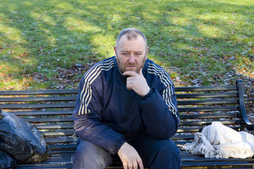 man with depression sitting in a park