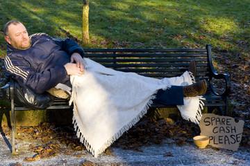 homeless man sleeping on park bench