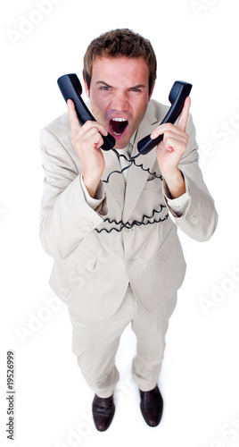 Stressed businessman yelling tangled up in phone wires