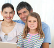 Little girl using a laptop with her parents