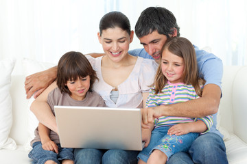 Jolly family using a laptop on the sofa