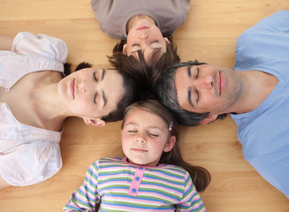 Merry family sleeping lying on the floor