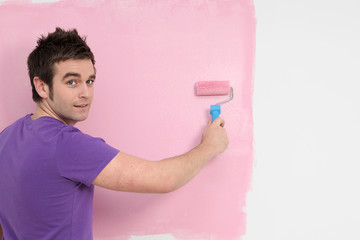 man painting wall, decorating new home