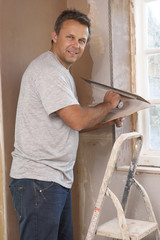 Plasterer Working On Interior Wall