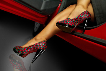 Long woman's legs in the shoes with red car