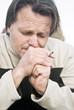 colour portrait of depressed man smoking cigarette