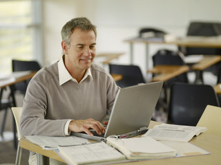 Professor working at laptop in classroom