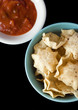 A bowl of tortilla chips with salsa bowl on black background