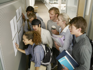 College students checking test scores in corridor