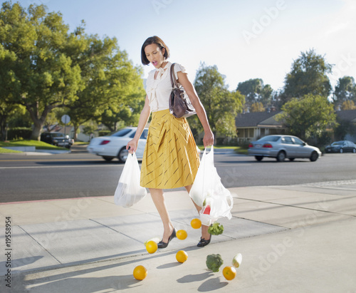 Woman dropping groceries on sidewalk