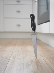 Close up of kitchen knife stuck in floor