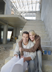 Couple with blueprints hugging on staircase of house under construction