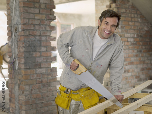 Man sawing wood at construction site